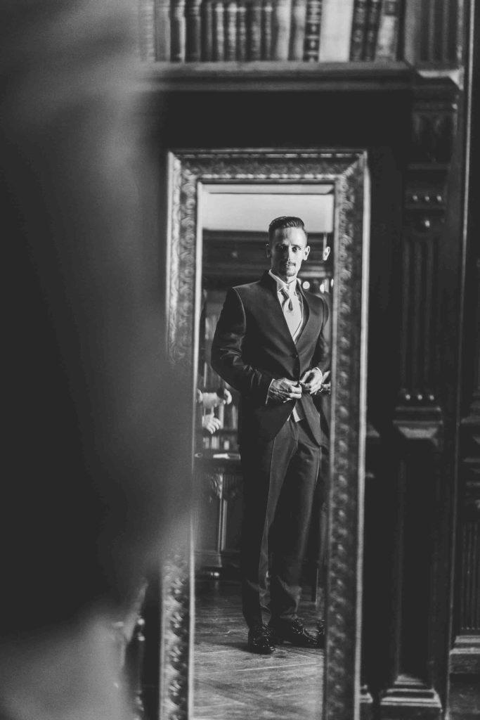 der Bräutigam betrachtet sich im Spiegel