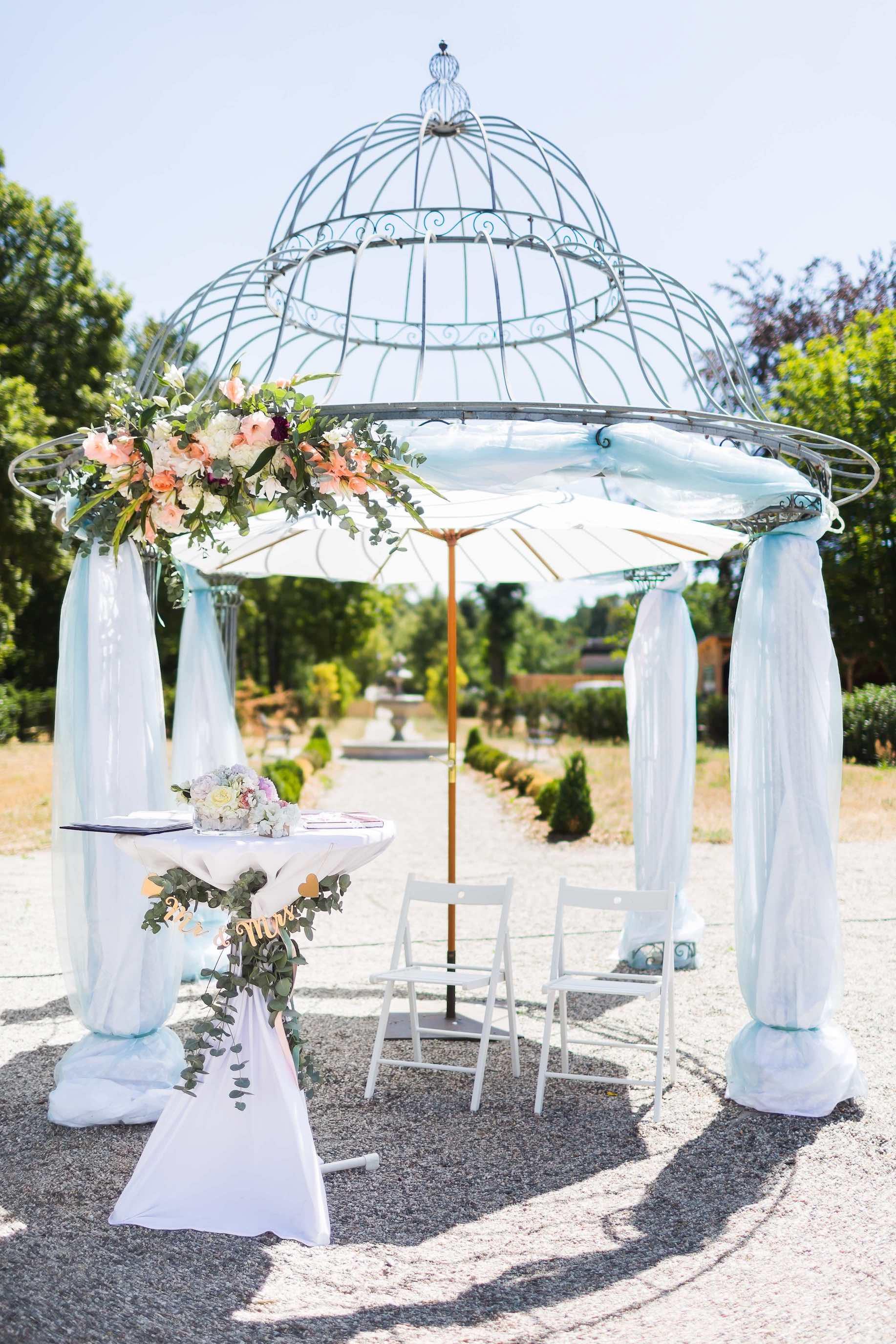 mit Blumen und Stoffen geschmückter Traupavillon