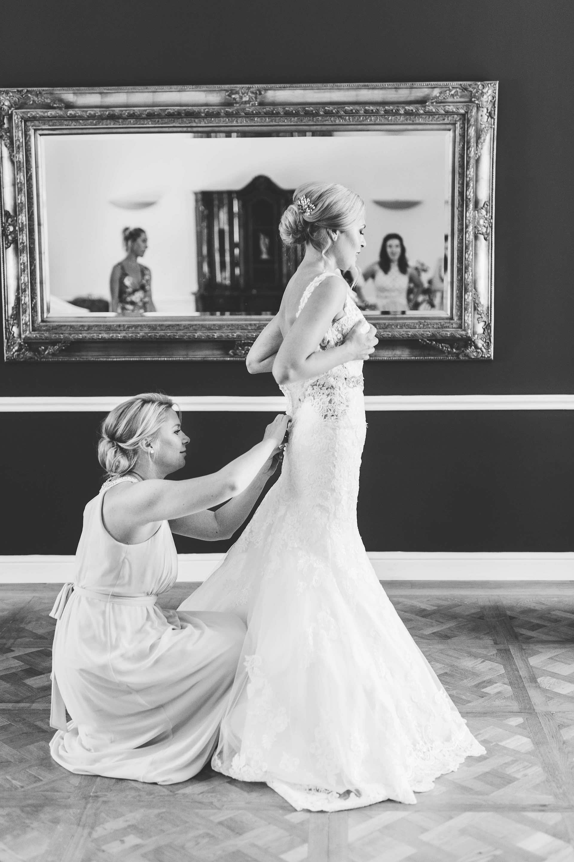 die Trauzeuginnen helfen der Braut beim Anziehen