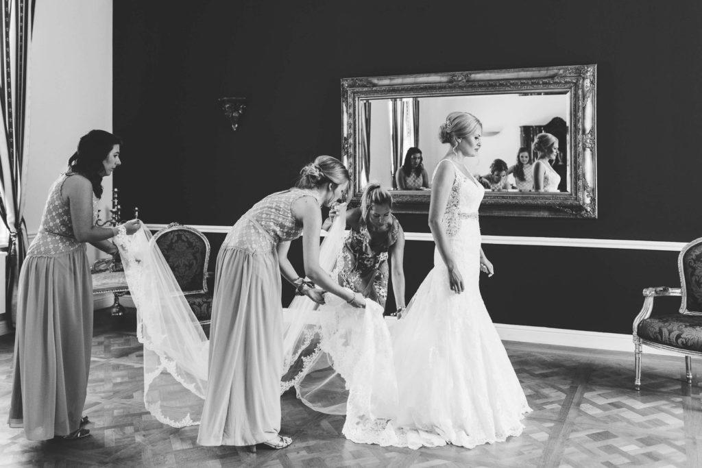 die Trauzeuginnen helfen beim Herrichten der Braut