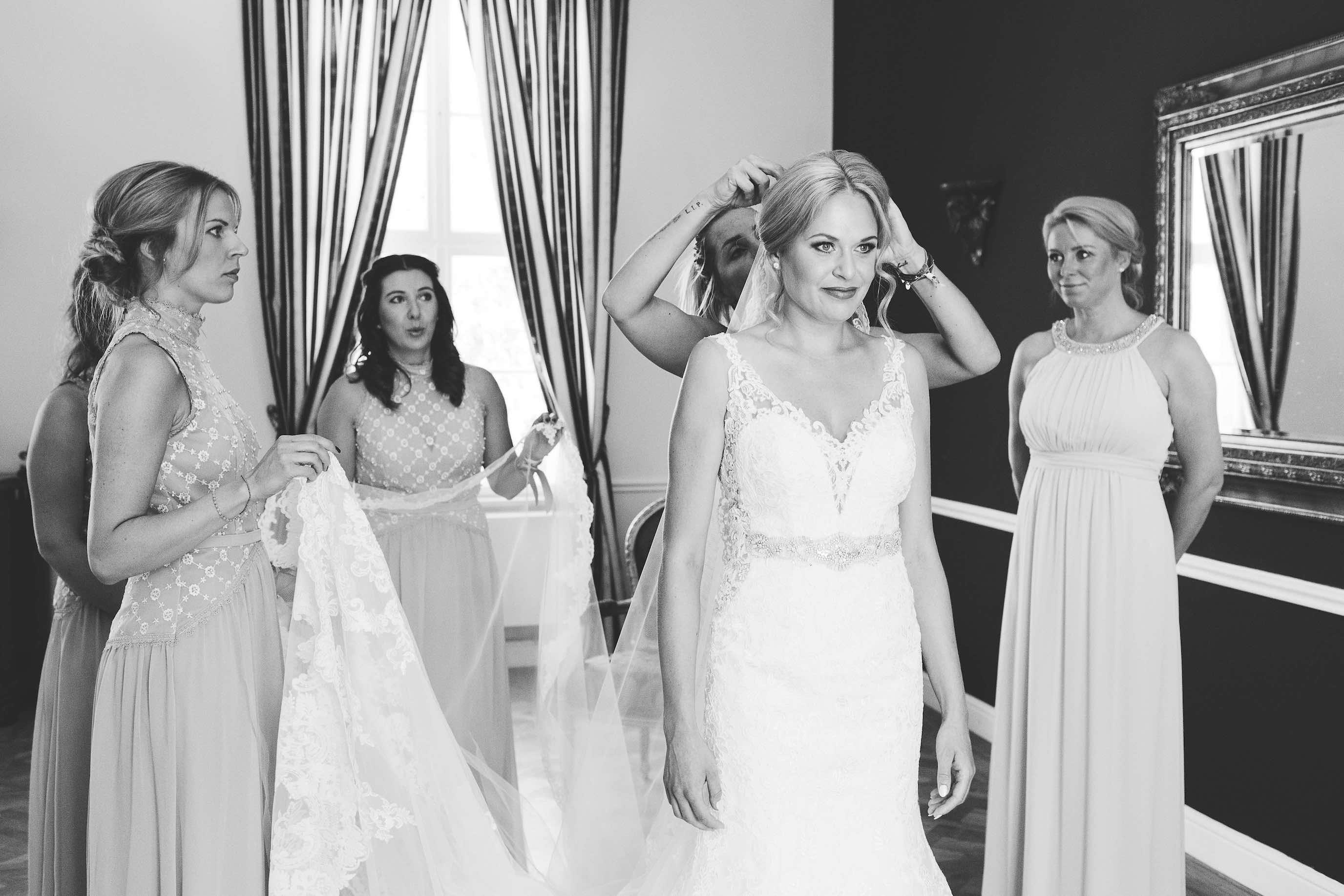 die Trauzeuginnen fixieren den Schleier der Braut