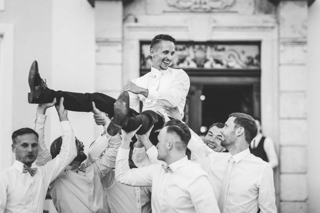 die Trauzeugen tragen ihren Bräutigam auf Händen
