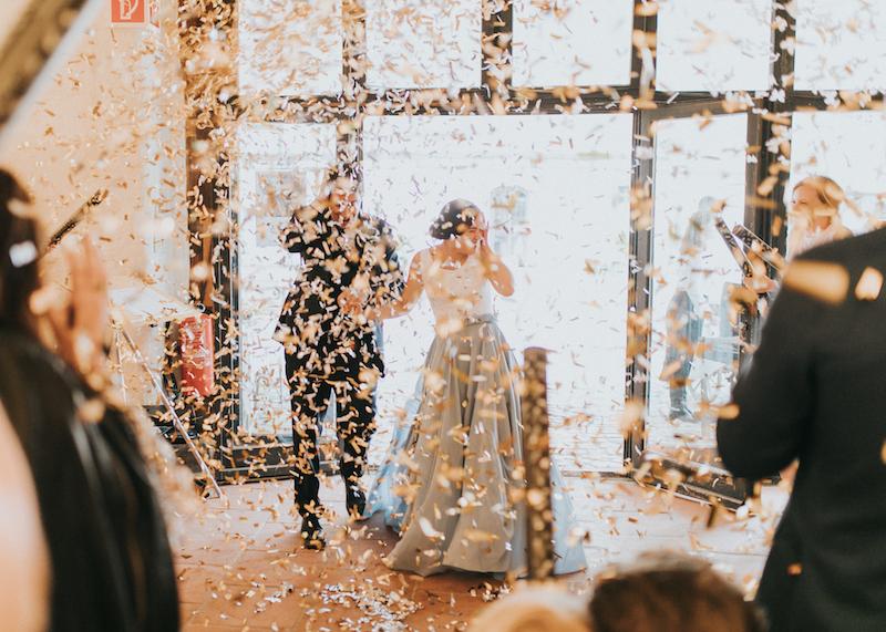 Brautpaar steht im Konfettiregen
